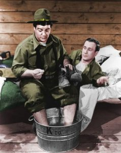 Bud Abbott and Lou Costello soaking their feet in a colorized photo from Buck Privates