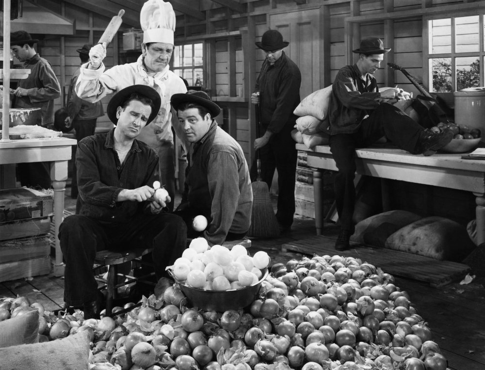 Publicity photo from Buck Privates, with Bud Abbott and Lou Costello peeling potatoes under Shemp Howard's supervision